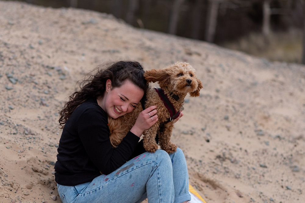 Artist laughing sat on Formby Beach holding pet cockapoo.