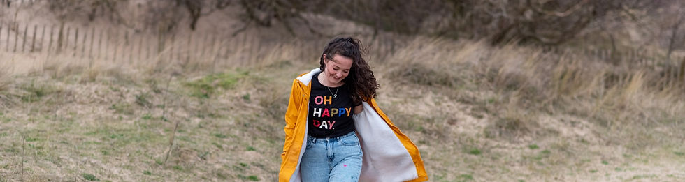 """Chesire artist walking on sand dunes near Liverpool wearing yellow rain coat and shirt that says """"oh happy day"""""""