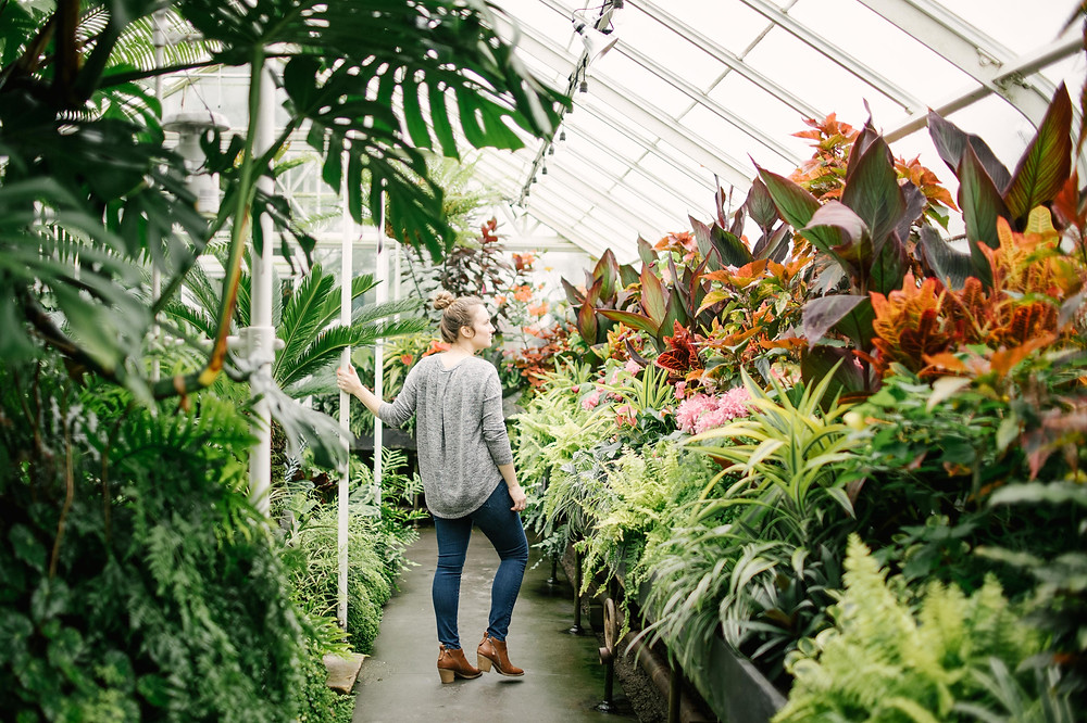White woman in greenhouse in Seattle surrounded by tropical plants