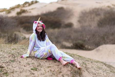 Chesire artist, Saz Winstanley, dressed in unicorn onesie at Formby Beach during her brand shoot.