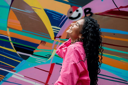 Personal trainer, Mia, Eyo, laughing up toward the sky in front of graffiti during Liverpool photoshoot.