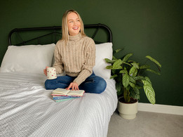 Yoga instructor reading and enjoying tea on bed.