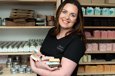 Liverpool soap maker, Clare Blasberry, owner of Skyn Bakery, cradling a collection of her eco-friendly rainbow soaps.