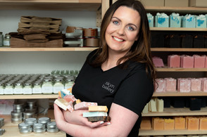 Soapmaker posing with her soaps