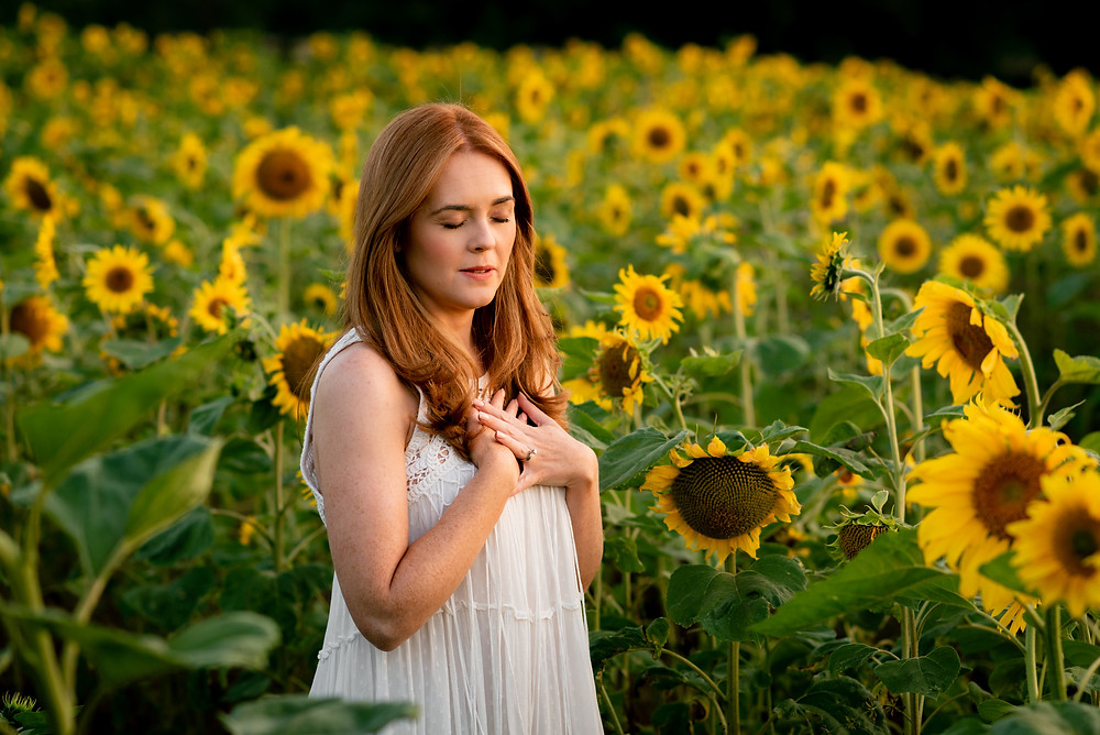 Red-haired woman mediating in a field of sunflowers