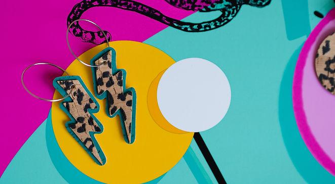Vegan cork leather leopard print earrings against colorful art print.