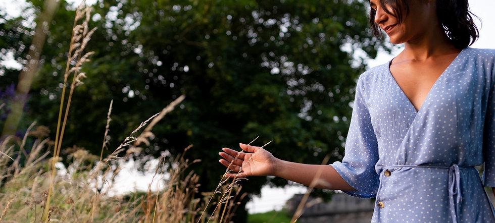 Lancashire hypnotherapist running hands through weeds at Leeds Liverpool canal at sunset.