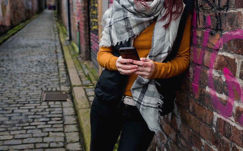 Woman texting against street art in Liverpool.