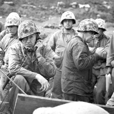 """""""Posto di comando di divisione – Ufficiali della 5° divisione di marina dirigono le operazione della loro unità da una posizione protetta da sacchetti di sabbia a Iwo Jima. Sullo sfondo da sinistra a destra: il brigadiere generale Leo D. Hermle, assistente al comandante di divisione; il maggiore generale Keller E. Rockey (con il telefono), comandante di divisione; il colonnello James Shaw, ufficiale delle operazioni e il colonnello Ray Robinson, capo divisione dello staff"""""""