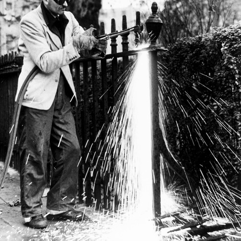 Un operaio sta usando un bruciatore all'acetilene sulla cancellata della statua del Duca di Bedford in Russell Square. Anche il metallo di cui erano fatte le cancellate veniva infatti usato per fare gli aeroplani