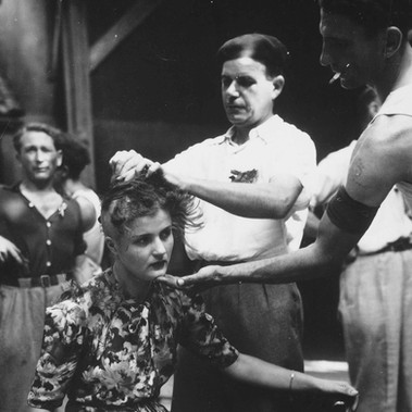 """This girl pays the penalty for having had personal relations with the Germans. Here, in the Montelimar area, France, French civilians shave her head as punishment"""