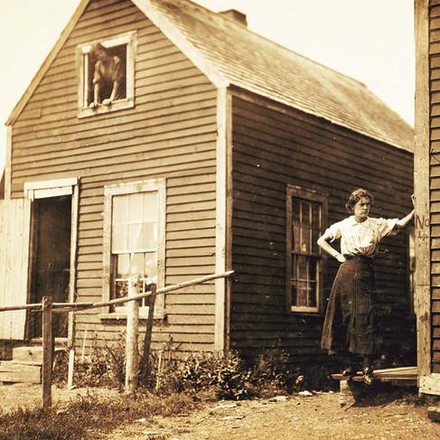 """""""Le condizioni abitative nell'insediamento di Seacoast Cannery # 7, Eastport, Me., non sono molto buone. Questa è la casa della famiglia Goodell. Vivono qui tutto l'anno in questi alloggi temporanei. Il padre lavora nel vicino mulino. Quattro o cinque dei bambini sono nell'industria dell'inscatolamento. Clarence, 8 anni; George, 9 anni; Lottie, 12 anni; """"Guadagna un paio di dollari alcuni giorni""""; Violet, 15 anni, """"ha guadagnato quattro dollari al giorno facendo imballaggi a volte"""" (vedi finestra in alto)"""" """"Housing conditions in settlement at Seacoast Cannery #7, Eastport, Me., not very good. This is the home of the Goodell family. They live here all the year in these temporary quarters. The father works in the mill nearby. Four or five of the children are in the canneries. Clarence, 8 years; George, 9 years; Lottie, 12 years; """"Makes a couple of dollars some days""""; Violet, 15 years, """"has made four dollars a day packing at times,"""" (see upper window)""""  Eastport, Maine, USA Agosto 1911 Foto di Lewis Wickes Hine © Courtesy Library of Congress, Prints & Photographs Division, National Child Labor Committee Collection"""