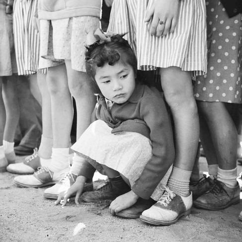 """""""A little girl evacuee of Japanese descent watches the Memorial Day Services. Evacuee Boy Scouts took a leading part in the ceremony held at this War Relocation Authority center""""  May 30, 1942 Manzanar Relocation Center, Manzanar, California  Author Francis Stewart, War Relocation Authority photographer  © courtesy U.S. National Archives and Records Administration"""