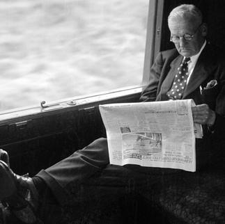 Uomo d'affari legge il giornale su un treno diretto alla stazione di St. Pancas, Londra. L'immagine è stata scattata durante la produzione di un film sui trasporti in Gran Bretagna nel 1950