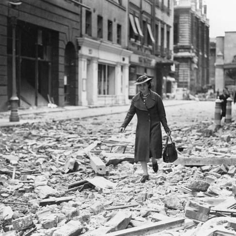 """""""Una donna, con la borsa della spesa in mano, procede tra le macerie di una strada del West End dove gli edifici sono stati danneggiati in raid recenti. La spesa doveva essere fatta. Era difficile camminare tra le macerie, ma questa donna lo faceva con un sorriso"""""""