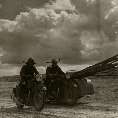 Membri della Brigata Motorizzata trasportano con le moto dei rami per costruire un rifugio