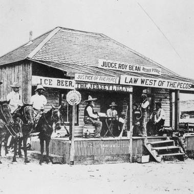 """""""Il giudice Roy Bean, la legge a Ovest del Rio Pecos, mentre tiene corte processando un ladro di cavalli nella vecchia città di Langtry, in Texas, nel 1900. Questo edificio era sia palazzo di giustizia che saloon. Non c'era nessun altro ufficiale di pace nella zona a quei tempi""""  Autore sconosciuto Courtesy National Archives"""