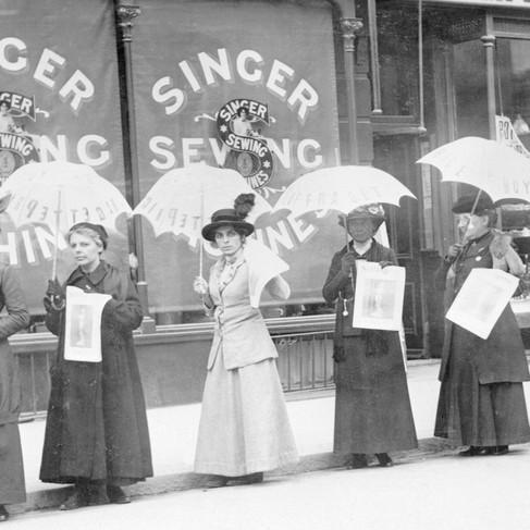 """Una """"parata con gli ombrelli"""" per la vendita del giornale «The Suffragette»"""