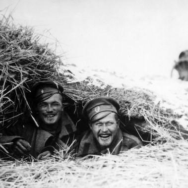 Due soldati russi sul fronte orientale sorridono al fotografo da un rifugio nascosto al nemico dalla paglia