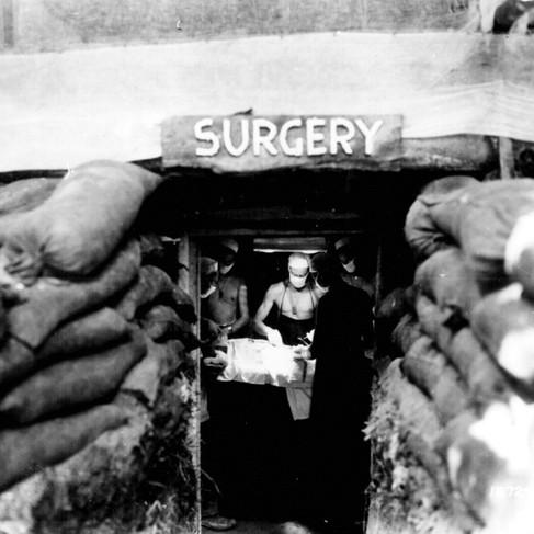 """""""In una sala operatoria sottoterra, dietro le linee del fronte a Bouganvile, un dottore dell'esercito Americano opera un soldato statunitense ferito da un cecchino giapponese"""""""