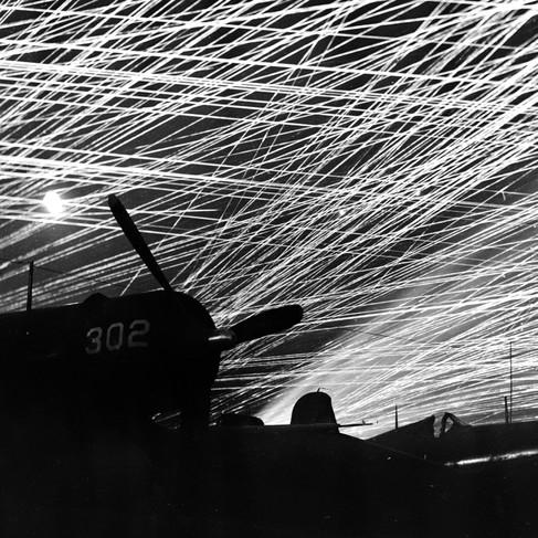 """""""Caccia Corsair della squadriglia """"Hell Belles"""" dei Marine Corps si stagliano contro il cielo reso un merletto dai proiettili traccianti. Questa foto è stata fatta nel corso di un raid aereo giapponese su un campo d'aviazione di Yontan"""""""