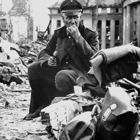 """""""This Nazi officer is eating his words, and a can of C-rations, in the ruins of Saarbrücken. The day we hung our washing on this Siegfried line stronghold, we of the Seventh linked up with Third Army armor west of Kaiserlautern. Was that a day!"""""""