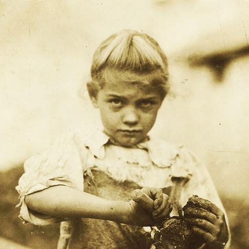 """""""Rosie di 7 anni. Sguscia regolarmente ostriche. È il suo secondo anno. Analfabeta. Lavora tutto il giorno. Sguscia solo alcune pentole di ostriche al giorno. (Mentre mostra come si fa). Varn & Platt Canning Co."""" """"7-year old Rosie. Regular oyster shucker. Her second year at it. Illiterate. Works all day. Shucks only a few pots a day. (Showing process) Varn & Platt Canning Co.""""  Febbraio 1913 Bluffton, South Carolina, USA Foto di Lewis Wickes Hine © Courtesy Library of Congress, Prints & Photographs Division, National Child Labor Committee Collection"""