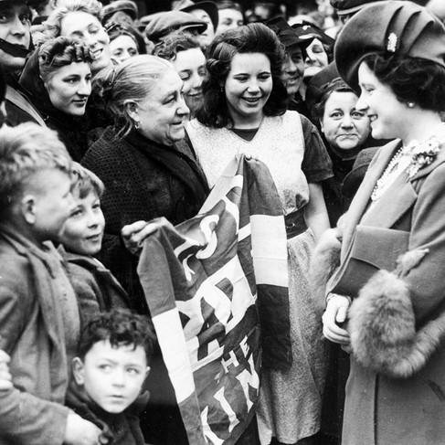 """La Regina mentre parla con un'abitante di East London che tiene in mano una bandiera con scritto """"God save the King"""", durante una delle visite della famiglia reale ai distretti bombardati dell'area di East London. La regina Elisabetta (1900-2002) era la moglie di Re Giorgio VI (1895-1952) e la madre dell'attuale regina Elisabetta II"""