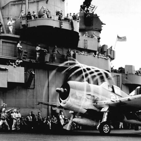 """""""Statica dinamica. Il movimento delle pale dell'elica forma """"un'aura"""" intorno a questo F6F sulla USS Yorktown. Infatti il movimento dell'aereo in avanti, mentre le lame delle eliche ruotano, crea un alone che dà profondità e prospettiva"""""""