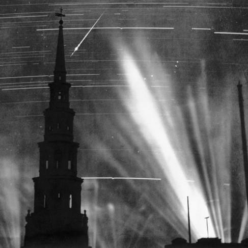 """""""Una macchina fotografica con treppiede è stata posizionata sulla sommità di un tetto di Londra per un'ora e mezza per riprendere gli attacchi aerei. I proiettori individuano i velivoli invasori: si può vedere la scia di un aereo tedesco in fiamme mentre precipita in direzione del campanile"""""""