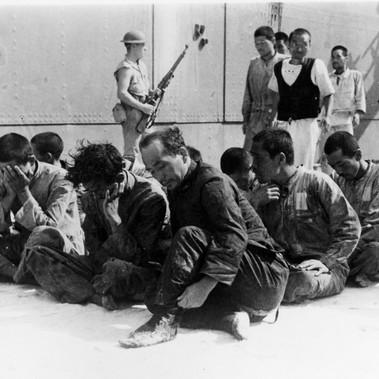 """""""Prigionieri di Guerra giapponesi guardati a vista da soldati americani, dopo essere stati recuperati da una scialuppa di salvataggio dalla USS Ballard (AVD-10) nel giugno 1942. Sono i sopravvissuti della portaerei affondata Hiryu. Dopo essere stati trattenuti per alcuni giorni a Midway, sono stati mandati a Pearl Harbor il 23 giugno a bordo della USS Sirius (AK-15), arrivando il primo luglio. Da notare il marine di guardia al centro dietro il gruppo di prigionieri armato con un fucile M1903 Springfield"""""""