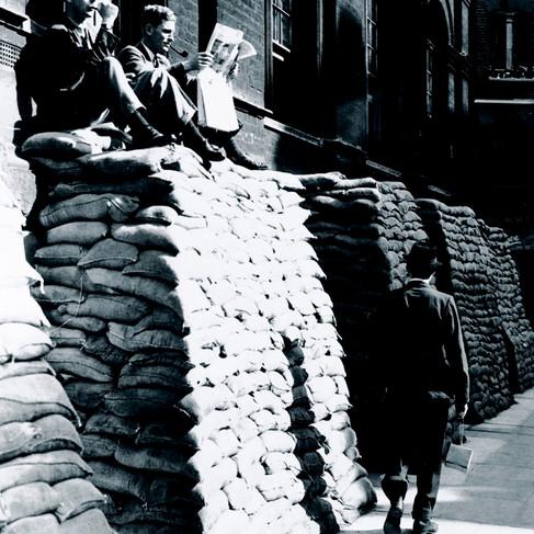 """""""Due amanti della tintarella si crogiolano al sole comodamente seduti sui sacchi di sabbia durante l'ora del pranzo ieri a Londra"""""""