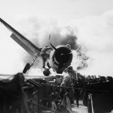 """Crash landing of F6F on flight deck of USS ENTERPRISE while enroute to attack Makin Island. Lieutenant Walter Chewning, catapult officer, clambering up the side of the plane to assist pilot, Ens. Byron Johnson, from the flaming cockpit"""