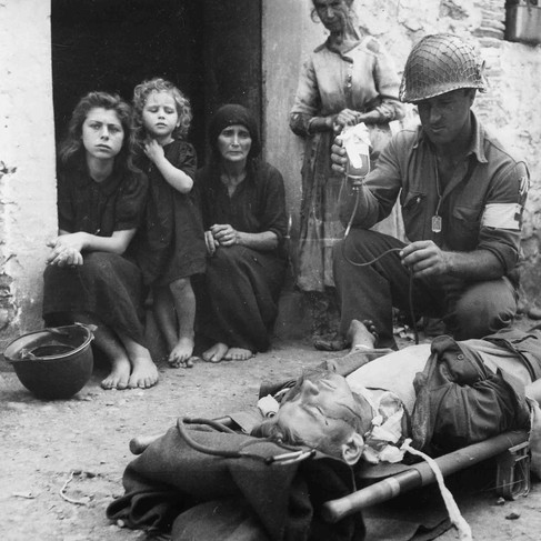 """""""Private Roy Humphrey of Toledo, Ohio, is being given blood plasma by Private First Class Harvey White of Minneapolis, Minnesota, after he was wounded by shrapnel"""""""