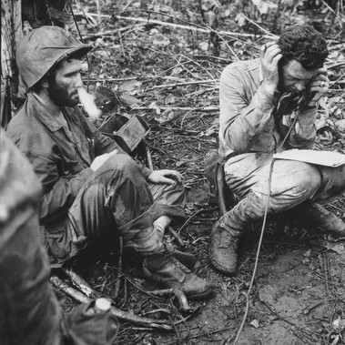 """Lieutenant Colonel John Weber, commanding officer of a Marine battalion on Cape Gloucester, sitting on his helmet, receives a report from one of his company commanders. Private first class Vincent Miley, looking on, blows cigarette smoke out of his nose"""