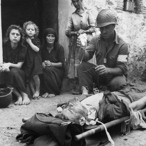 """""""Private Roy Humphrey of Toledo, Ohio, is being given blood plasma by Private First Class Harvey White of Minneapolis, Minnesota, after he was wounded by shrapnel""""  August 9, 1943  Sicily, Italy Author unknown or not provided © courtesy U.S. National Archives and Records Administration"""