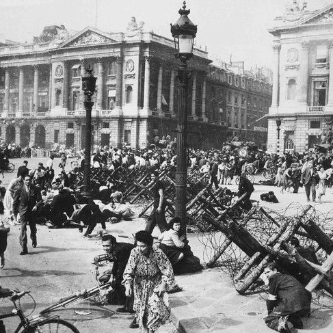 """""""Crowds of Parisians celebrating the entry of Allied troops into Paris scatter for cover as a sniper fires from a building on the Place de la Concorde. Although the Germans surrendered the city, small bands of snipers still remained.""""  August 26, 1944 Paris, France Author unknown or not provided © courtesy U.S. National Archives and Records Administration"""
