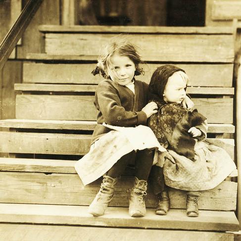 """""""La piccola Julia si prende cura della bimba a casa. Tutti quelli più grandi sono in fabbrica. Fa anche la sgusciatrice di ostriche. Alabama Canning Co."""" """"Little Julia tending the baby at home. All the older ones are at the factory. She shucks also. Alabama Canning Co.""""  Febbraio 1911  Bayou La Batre, Alabama, USA Foto di Lewis Wickes Hine © Courtesy Library of Congress, Prints & Photographs Division, National Child Labor Committee Collection"""
