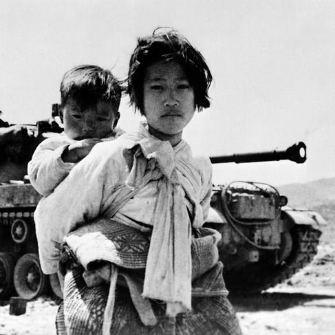 Ragazzina coreana con il fratello sulle spalle a nord di Seul durante la guerra di Corea