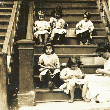 """Un tipico gruppo di lavoratrici sui gradini della scalinata della signora Dolan, 279 Highland Street, Roxbury, Mass"" ""Typical group of workers on tags. Steps of Mrs. Dolan, 279 Highland Street, Roxbury, Mass"" Agosto 1912  Roxbury, Massachusetts, USA Foto di Lewis Wickes Hine © Courtesy Library of Congress, Prints & Photographs Division, National Child Labor Committee Collection"