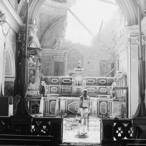 """""""Private Paul Oglesby, 30th Infantry, standing in reverence before an altar in a damaged Catholic Church.""""   July 23, 1943 Acerno, Sicily, Italy Author unknown or not provided © courtesy U.S. National Archives and Records Administration"""
