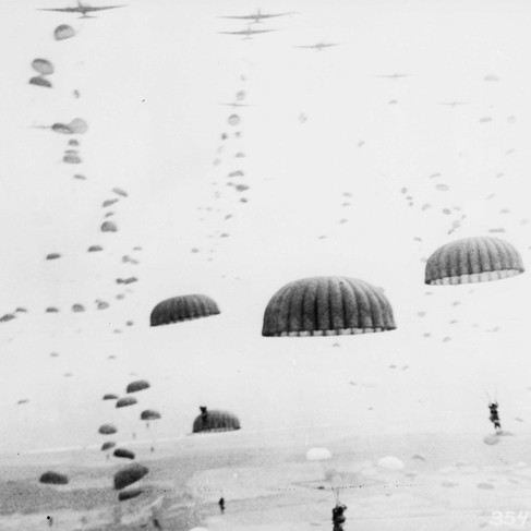 """""""Parachutes open overhead as waves of paratroops land in Holland during operations by the 1st Allied Airborne Army.""""  September 1944 Holland Author unknown or not provided © courtesy U.S. National Archives and Records Administration"""