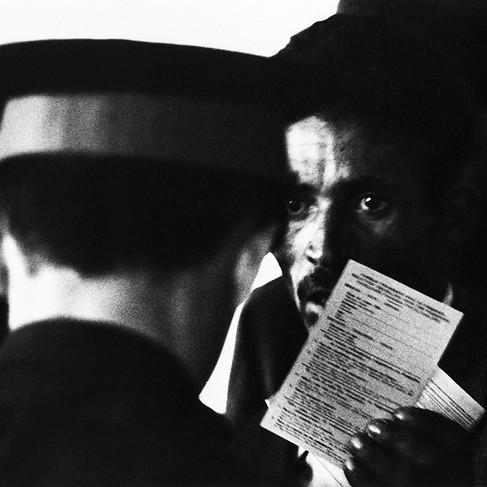 Il diritto al lavoro dei lavoratori migranti. Un lavoratore migrante nordafricano mostra i documenti al suo arrivo a Marsiglia