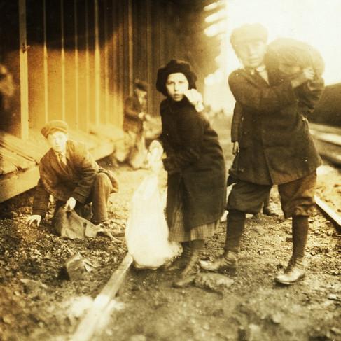 """Mentre rubano carbone dal deposito della ferrovia"" ""Stealing coal from railroad coal-yard"" 29 gennaio 1917 Boston, Massachusetts, USA Foto di Lewis Wickes Hine © Courtesy Library of Congress, Prints & Photographs Division, National Child Labor Committee Collection"