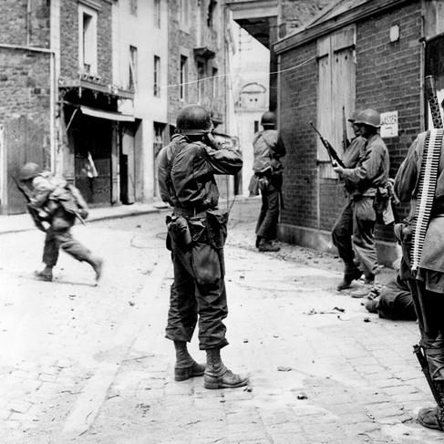 Combattimenti nelle strade a Saint Malo: soldati americani cercano di snidare un cecchino tedesco