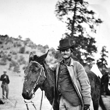 """""""Fred W. Loring in completo da campagna, con il suo mulo Evil Merodach"""".  La foto è stata scattata 48 ore prima che venisse brutalmente assassinato dagli Apache-Mohaves mentre era sulla strada che porta da Prescott (Territori dell'Arizona) a San Bernardino (California). Loring, giornalista aggregato alla spedizione Wheeler come corrispondente, stava tornando a Est """" … con la mente piena di rare avventure e paesaggi straordinari …""""   1871  Foto di Timothy H. O'Sullivan, autore di fama internazionale grazie alle sue immagini della Guerra Civile Americana e dell'Ovest degli Stati Uniti Courtesy National Archives"""