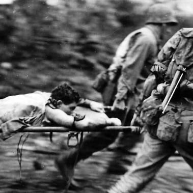 Un marine ferito viene trasportato all'infermeria lontano dalla prima linea sotto il fuoco giapponese