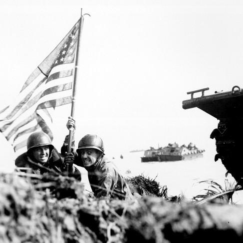 """""""La Prima bandiera a Guam, agganciata all'albero di una barca. Due ufficiali statunitensi piantano la bandiera americana su Guam otto minuti dopo che le truppe d'assalto dei marine e dell'esercito americano sono sbarcate sull'isola del Pacifico Centrale il 20 luglio 1944"""""""