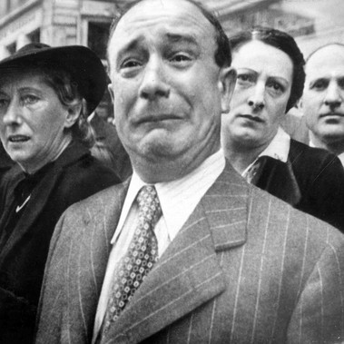 """A Frenchman weeps as German soldiers march into the French capital Paris, after the Allied armies had been driven back across France"""