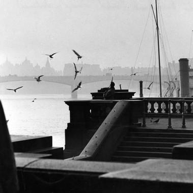 Un uomo sulla passeggiata dell'Embankment a Londra mentre guarda il Tamigi in direzione del ponte di Waterloo
